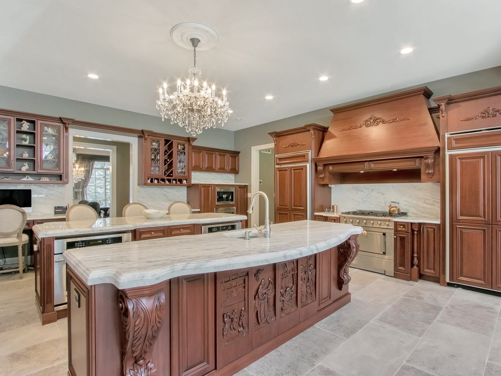 The gourmet kitchen has two oversized Carrera marble islands and a La Cornue cooking stove.