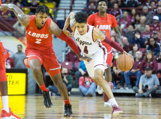 Jojo Zamora, pushes down court with UNM's Vance Jackson, during the first half of the NMSU/ UNM game at the Pan American Center, Tuesday December 4, 2018. NMSU beat UNM 100 to 65.