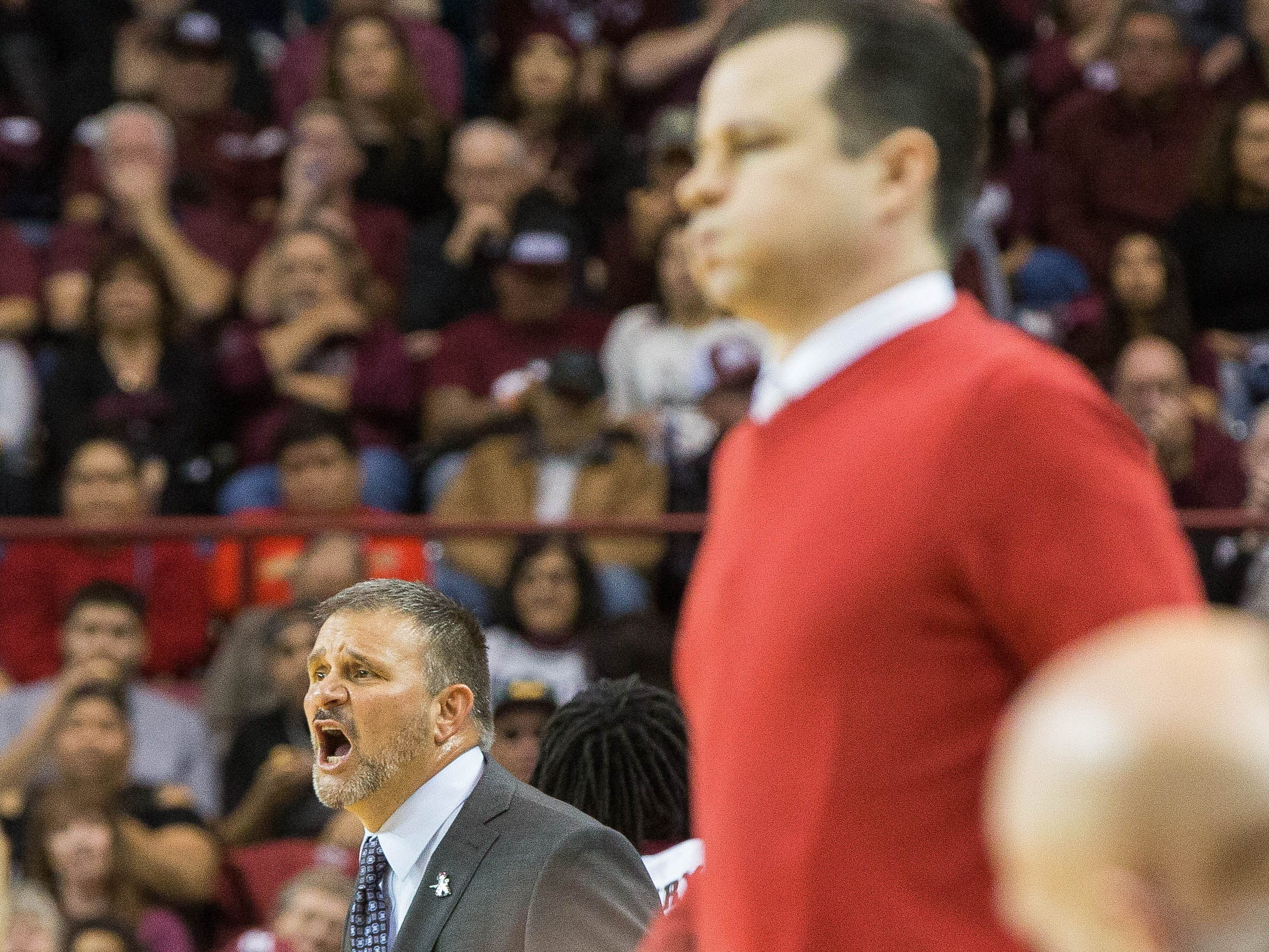 Chris Jans, headcoach at New Mexico State University yells to his players as University of New Mexico headcoach Paul Weir watchs his team with a look of frustration. Tuesday December 4, 2018 at the Pan American Center.