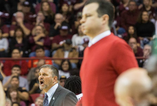 Chris Jans, head coach at New Mexico State University yells to his players as University of New Mexico head coach Paul Weir watches his team with a look of frustration. Tuesday December 4, 2018 at the Pan American Center.