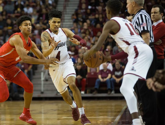 Jabari Rice, (10) passes the ball to Jojo Zamora,(4) as he pushes past Lobo's Tavian Percy, (4), during the first half of the New Mexico State University/ University of New Mexico match up, Tuesday December 4, 2018 at the Pan American Center.
