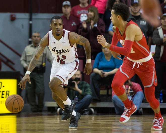 AJ Harris, (12) heads down court as Anthony Mathis, (32) guards him , during the first half of the New Mexico State University/ University of New Mexico game, Tuesday December 4, 2018 at the Pan American Center.
