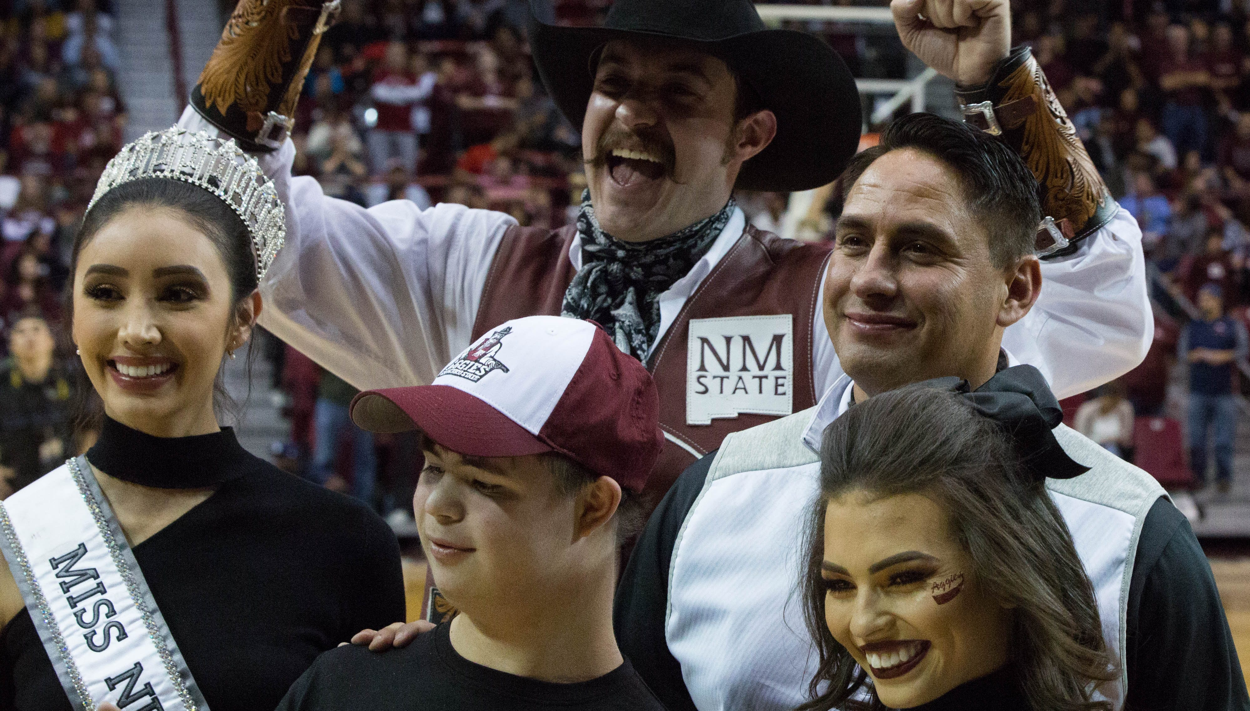 Howie Morales, New Mexico lieutenant governor, right, MAteo Query, 14, center, special olympian and Kristen Leyvay, Miss New Mexico 2018, taking photos and honored during the second half of the NMSU UNM game, Tuesday December 4, 2018. Lt. Governor Morales was honored as a distinguised alumnus and is his first public apperenace as the Lt. Gov. Elect.