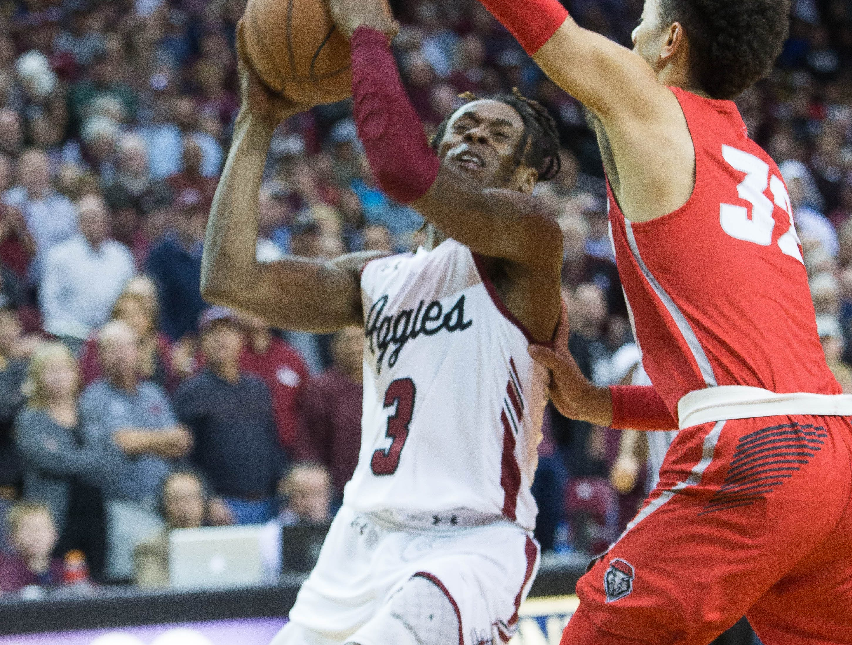 New Mexico State University's Terrell Brown, pushes past University of New Mexico's Anthony Mathis, during the first half of the game at the Pan American Center, Tuesday December 4, 2018. Aggies beat the Lobos 100 to 65.
