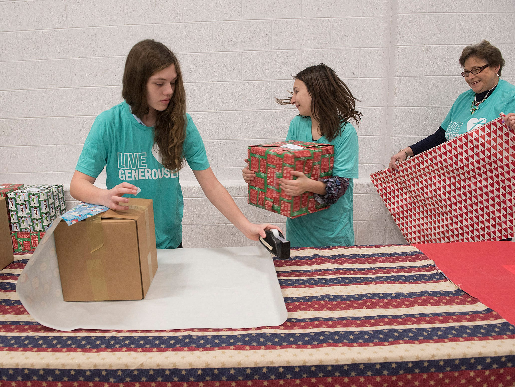 Samantha Emery and Dakota Gagnon wrap and move boxes. Principal Lori Bartholomew grabs another sheet of wrapping paper.