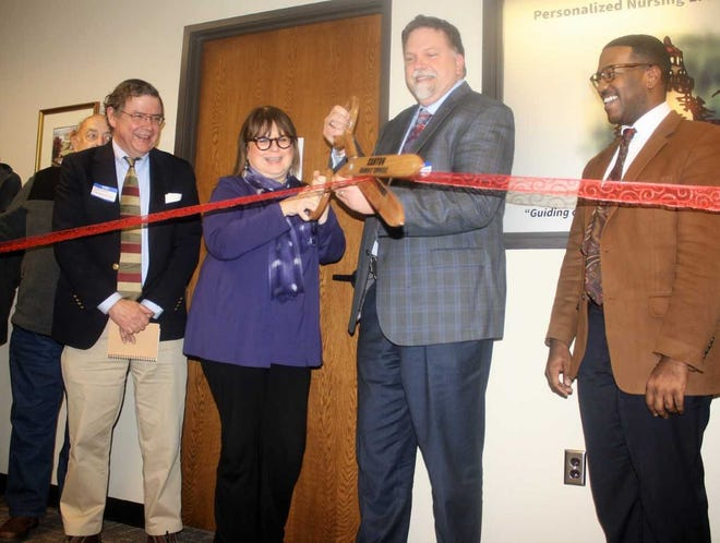 Canton Chamber of Commerce president Thomas Paden (right) looks on as Personalized Nursing Light House chief executive officer Joseph Paliwoda cuts the ribbon.