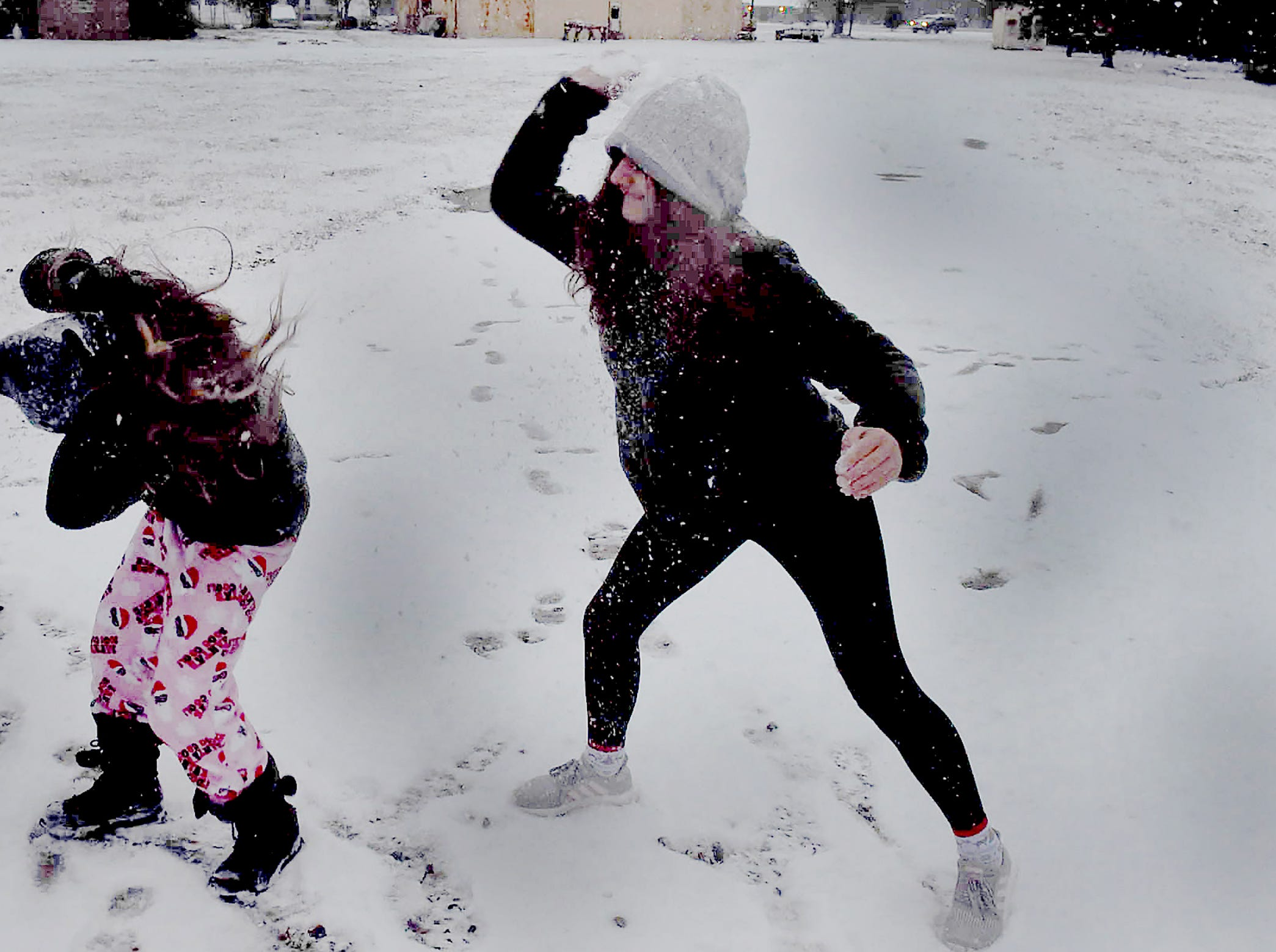 Prairie Laurent residents partake in a snowball fight late Tuesday afternoon as the snow begins to fall.