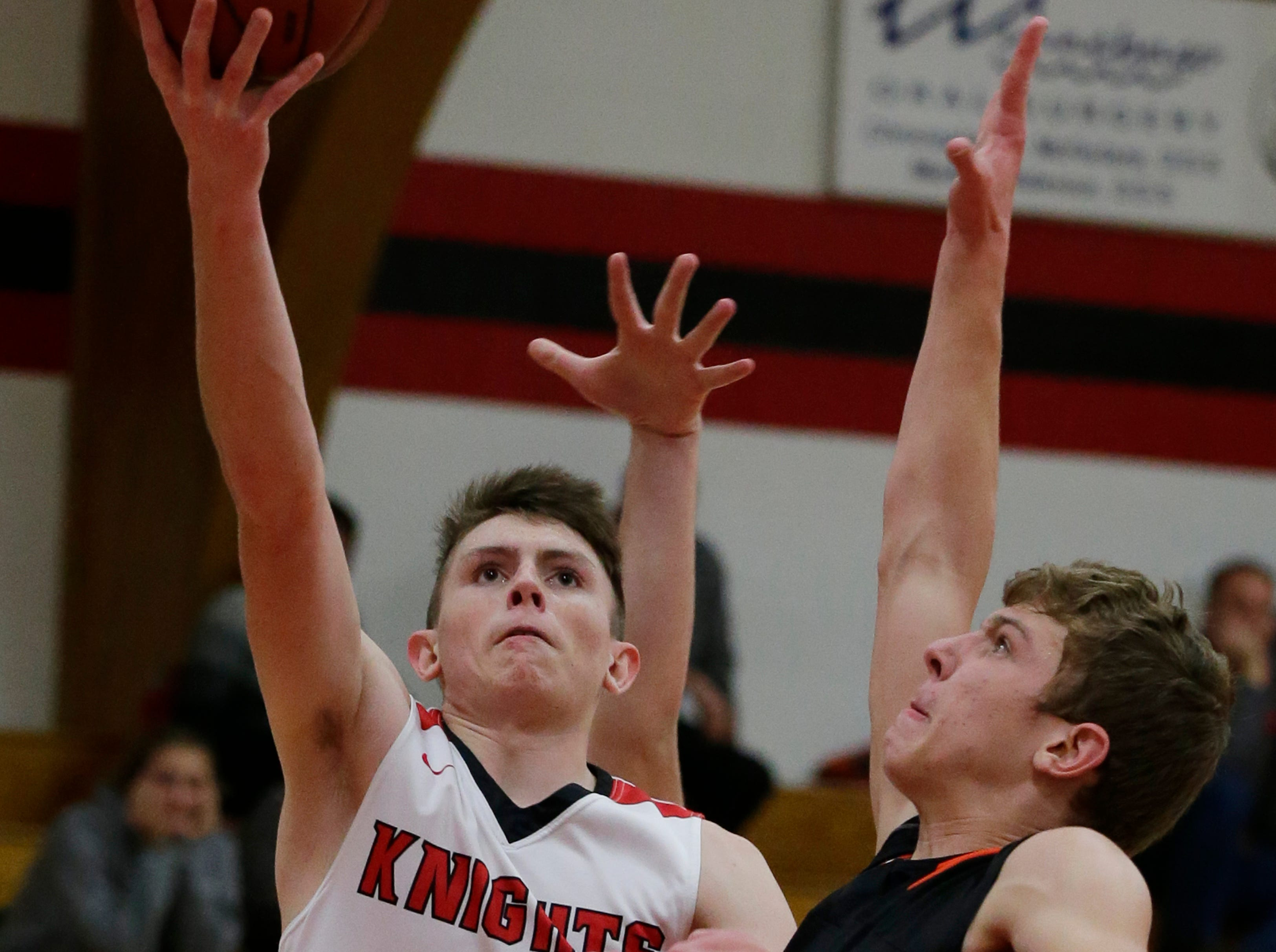 Lourdes Academy's Hayden Jones puts up a shot past Oakfield's Grant Bass.  Lourdes Academy Knights played Oakfield Oaks in boys basketball Tuesday, Dec. 4, 2018, at Lourdes Castle in Oshkosh, Wis.