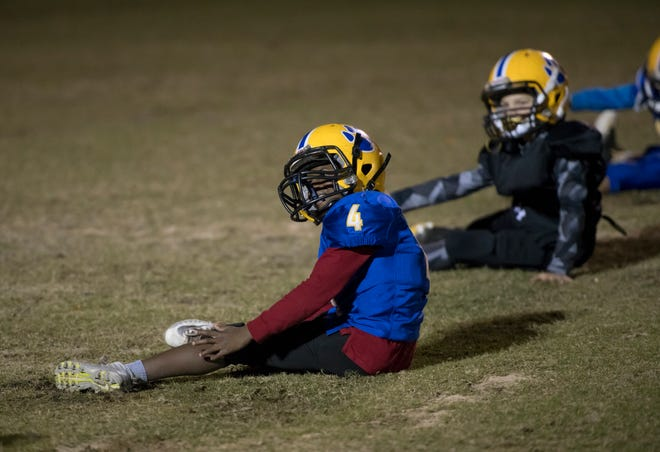 """Zayvion """"Boogie Woogie"""" Davis (4) and teammates stretch as the NEP 11U youth football team practices at the Roger Scott football field in Pensacola on Tuesday, December 4, 2018."""