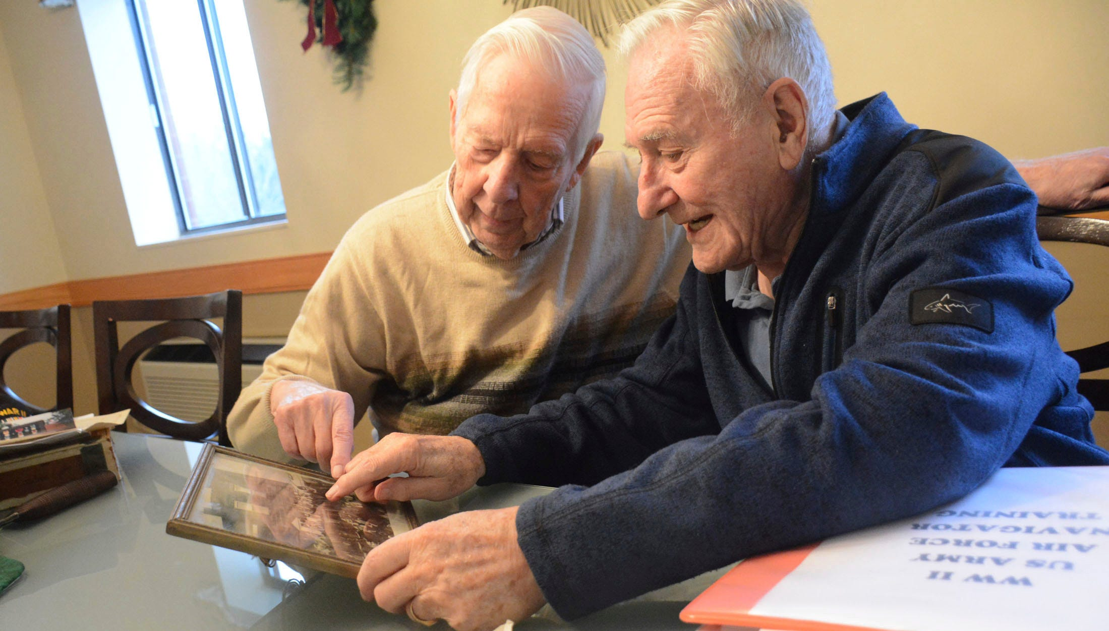 Bob Adams, 95, and Wes Piros, 95, share memories and stories about their days in the U.S. Army Air Force during WWII in Monroeville, Pennsylvania, on Nov. 28, 2018. Adams found a photograph taken 74 years ago of his unit during training and shared it with Piros, and to their surprise, both men were in the same picture and they soon discovered they spent time together training for the U.S. Army Air Force unit. The two gentlemen currently reside at Beatty Pointe Village in Monroeville.
