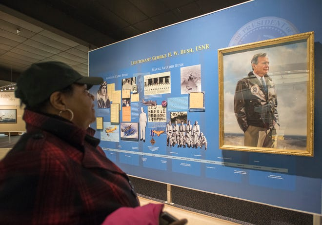 Mary Douglas, of Mobile, Alabama, pauses to view the President George H.W. Bush display in the art gallery at the National Naval Aviation Museum in Pensacola on Wednesday, December 5, 2018.