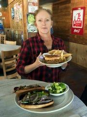 Monique Little serves up two of the favorite menu items, Jeffrey's Whole Hog Sauage sandwich, and the Cochon de lait, pulled pork sandwich at Jeffrey's Restaurant on Wednesday, Dec. 5, 2018. Jeffrey's is located on Baldridge Street next door to Kohl's