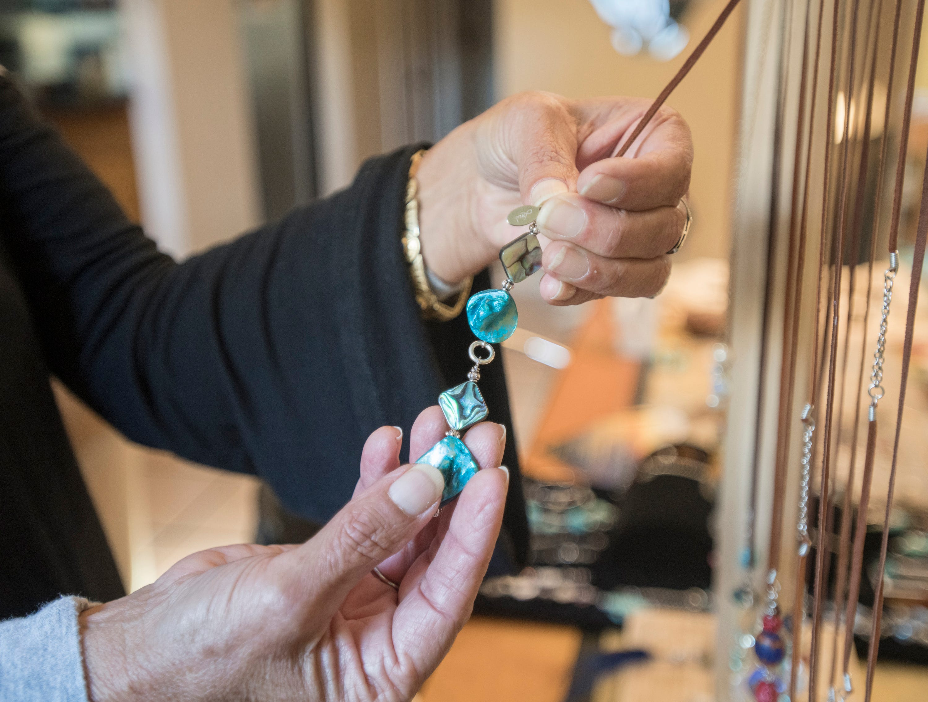 Mary Gentile, co-founder of I Love Me Knot, shows off a piece of jewelry in Gulf Breeze on Wednesday, December 5, 2018.  A portion of their proceeds aids those who have been impacted by suicide while reducing the stigma around mental illness.