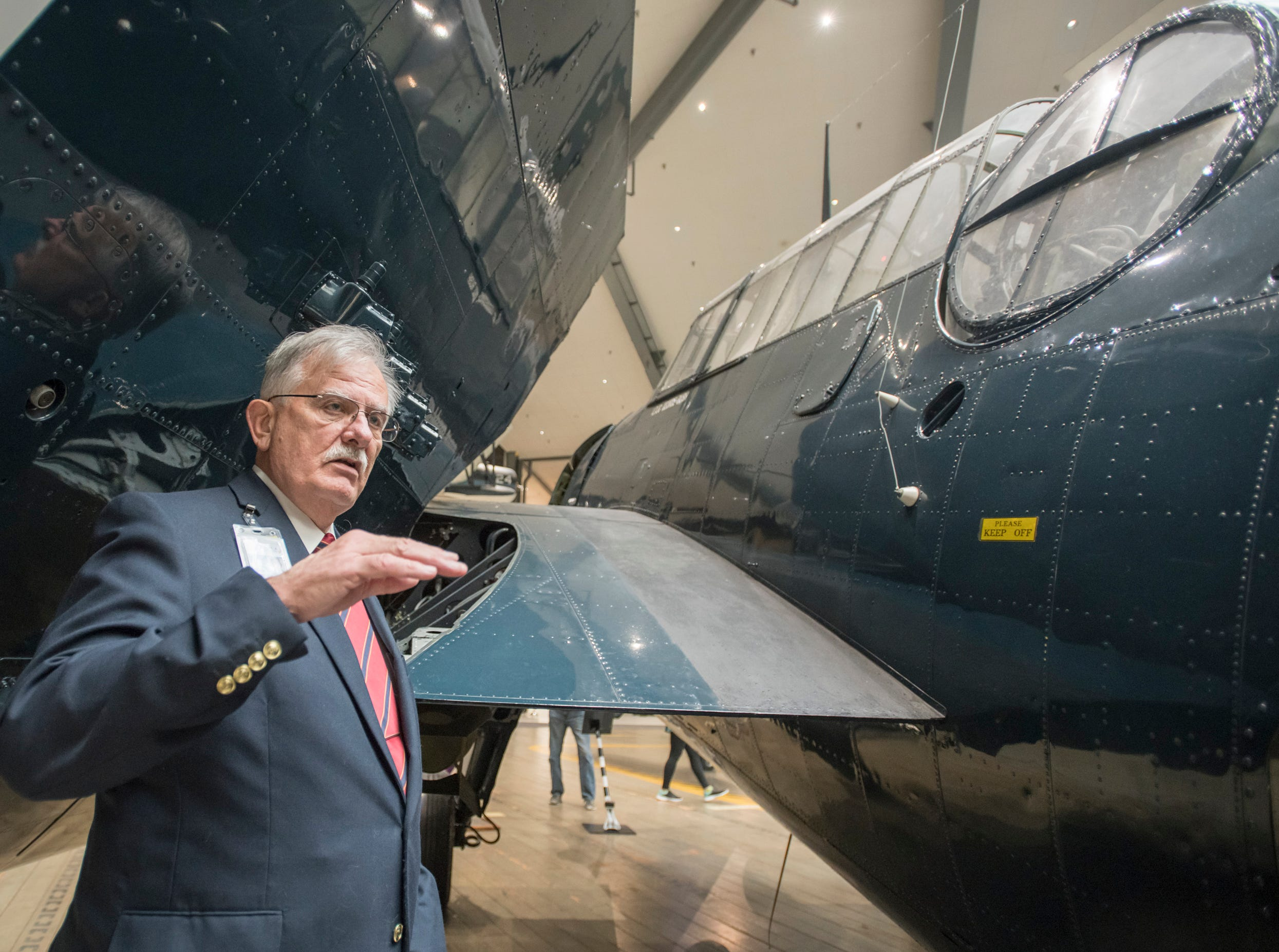 Docent Rick Fremgen talks about the TBM Avenger that is on display at the National Naval Aviation Museum in Pensacola on Wednesday, December 5, 2018.  This aircraft has George Bush's name stenciled on it in honor of President (then lieutenant junior grade) George H.W. Bush was shot down in this model during World War II.