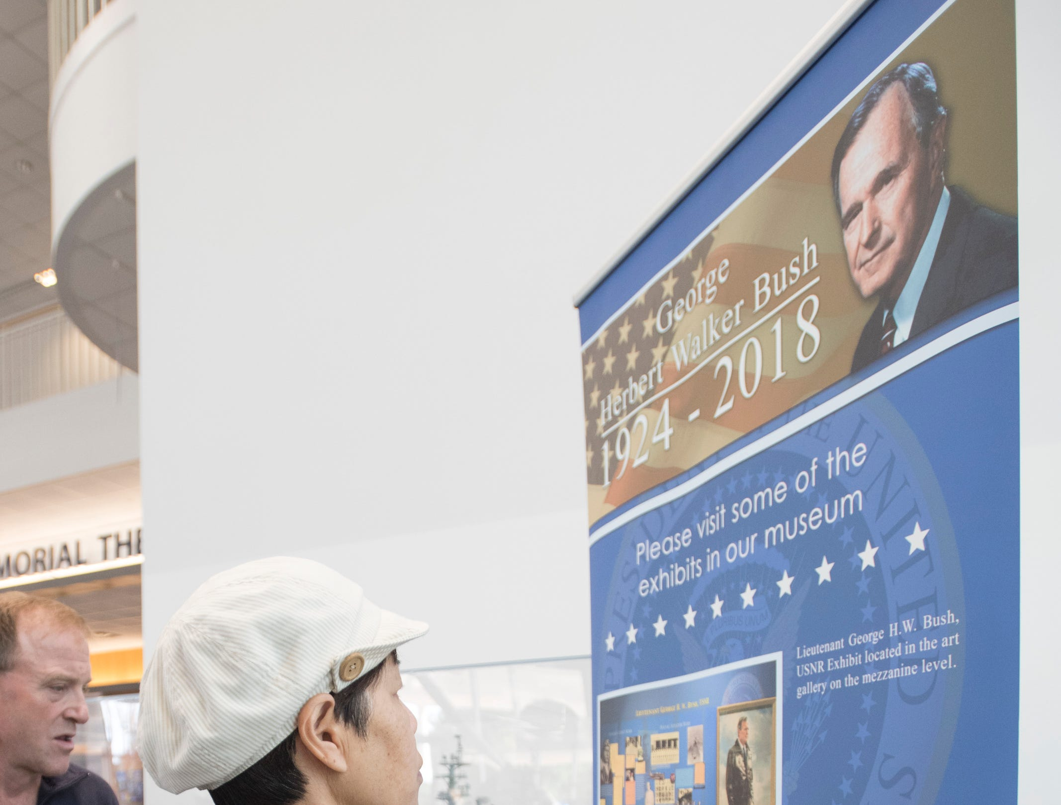 Kimmy Chen, of Los Angeles, reads the banner listing George H.W. Bush exhibits at the National Naval Aviation Museum in Pensacola on Wednesday, December 5, 2018.