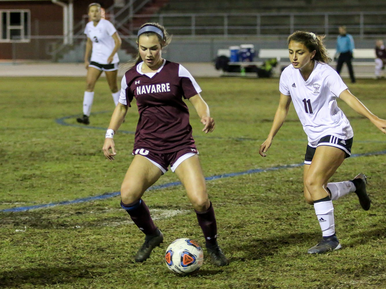 Navarre's Skylar Woods (18) works to keep the ball away from Niceville's Kayla Fernandez (11) in a District 1-4A showdown of unbeaten teams at Navarre High School on Tuesday, December 4, 2018. The game ended in a 1-1 tie.