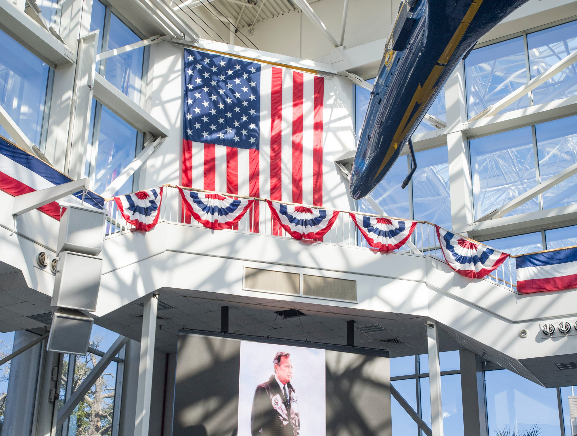 A portrait of President George H.W. Bush is displayed on the monitor in the atrium at the National Naval Aviation Museum in Pensacola on Wednesday, December 5, 2018.