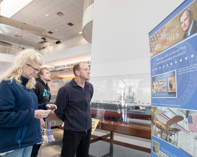 Sue, Tyler, and Bob Fuchs, of Savage, Minnesota, check out the banner listing George H.W. Bush exhibits at the National Naval Aviation Museum in Pensacola on Wednesday, December 5, 2018.
