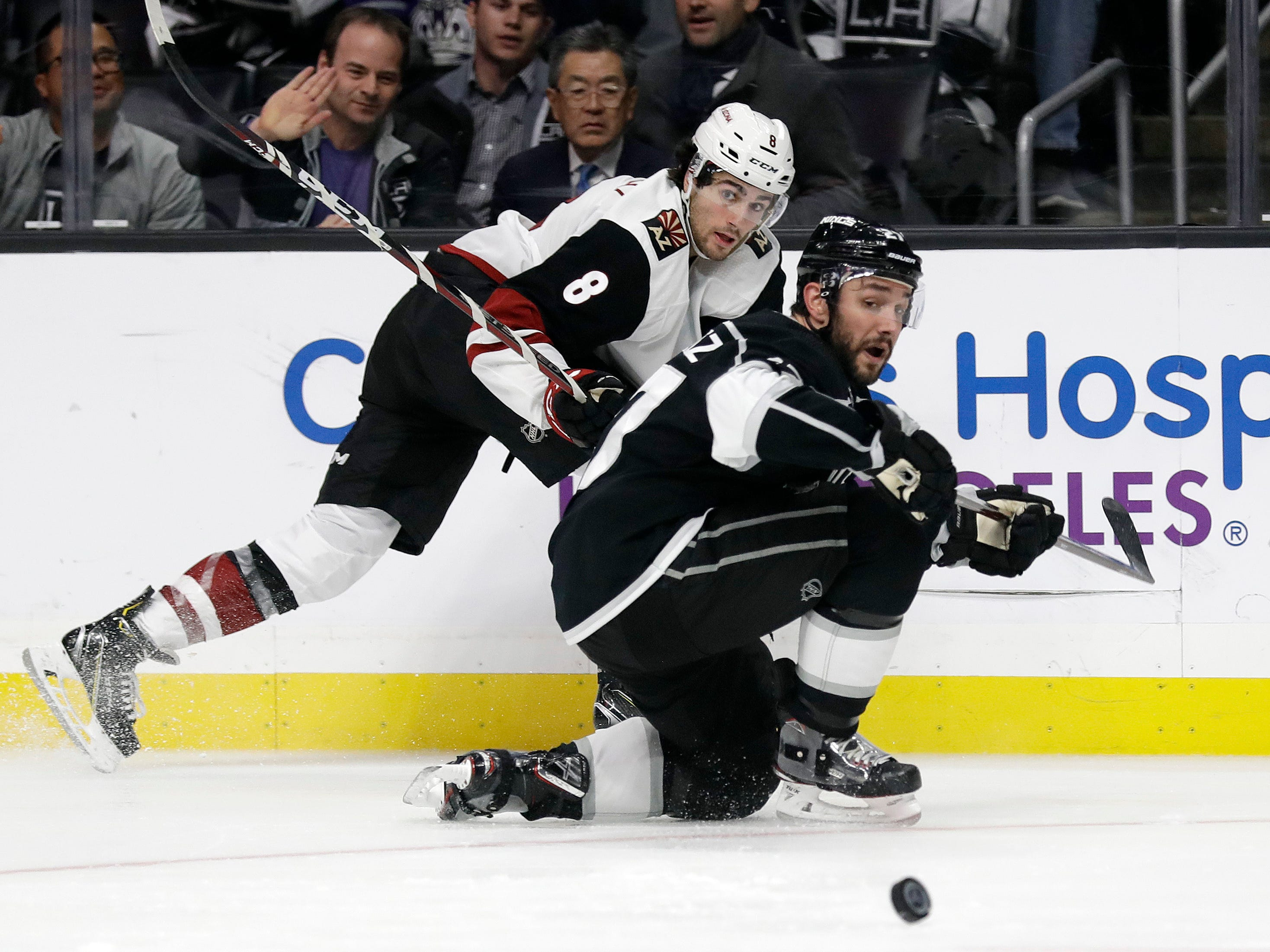 Arizona Coyotes' Nick Schmaltz, top, passes as Los Angeles Kings' Alec Martinez defends during the third period of an NHL hockey game Tuesday, Dec. 4, 2018, in Los Angeles.