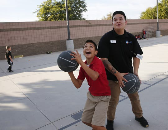Eder Soto, 11, plays with Armando Avelino, a program specialist at ICAN, an after-school program in Chandler on Nov. 20, 2018.