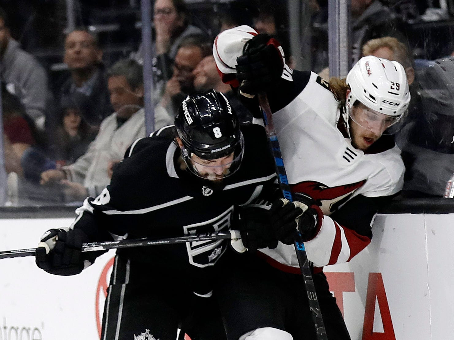 Los Angeles Kings' Drew Doughty, left, presses Arizona Coyotes' Mario Kempe against the boards during the third period of an NHL hockey game Tuesday, Dec. 4, 2018, in Los Angeles.