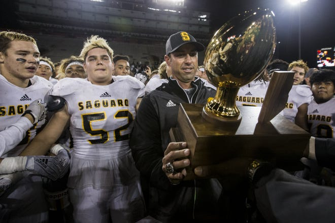Saguaro head coach Jason Mohns accepts the trophy after defeating Salpointe for the 4A State Championship on Friday, Nov. 30, 2018, at Arizona Stadium in Tucson, Ariz. Saguaro won, 42-16 for its sixth straight state football title.