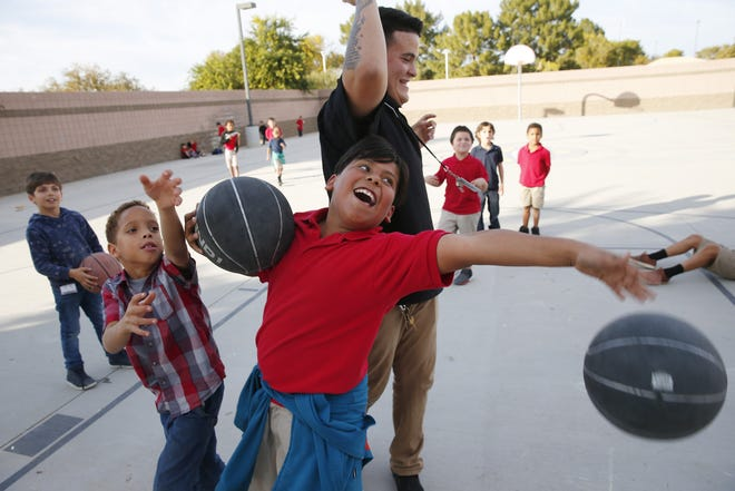Daelen Ransom (left), 8, and Cesar Mendoza, 10, play basketball with Armando Avelino, a program specialist at ICAN, an after-school program in Chandler on Nov. 20, 2018.