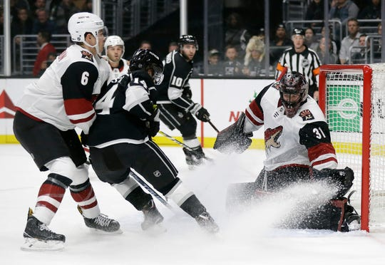 Arizona Coyotes goaltender Adin Hill, right, stops a shot from Los Angeles Kings' Brendan Leipsic, center, during the second period of an NHL hockey game Tuesday, Dec. 4, 2018, in Los Angeles.