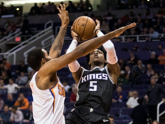 Sacramento Kings' De'Aaron Fox (5) shoots against Phoenix Suns' Trevor Ariza (3) during the first half of an NBA basketball game, Tuesday, Dec. 4, 2018, in Phoenix.