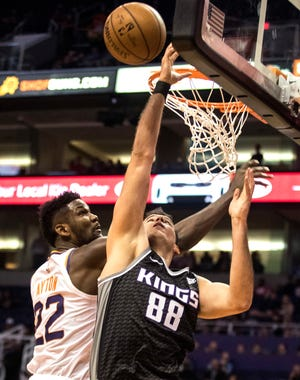 Sacramento Kings' Nemanja Bjelica (88) gets fouled by Phoenix Suns' Deandre Ayton (22) during the first half of an NBA basketball game, Tuesday, Dec. 4, 2018, in Phoenix.
