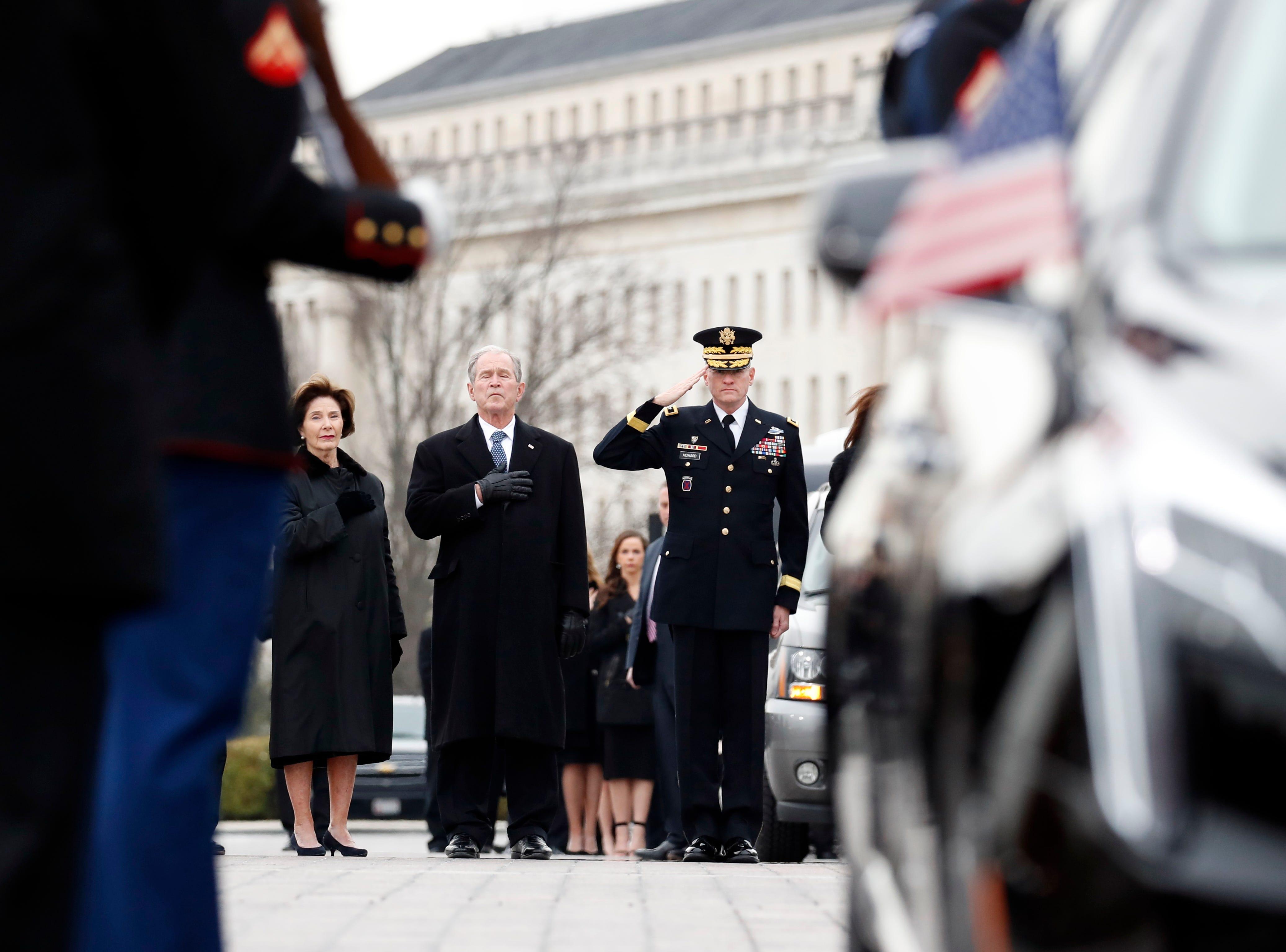 El ex presidente George W. Bush y la ex primera dama Laura Bush ponen sus manos sobre sus corazones mientras una guardia de honor militar de servicios conjuntos lleva el ataúd cubierto por la bandera del ex presidente de los Estados Unidos, George HW Bush, desde el Capitolio de los EE. UU. a la Catedral Nacional de Washington en diciembre 5, 2018 en Washington, DC.