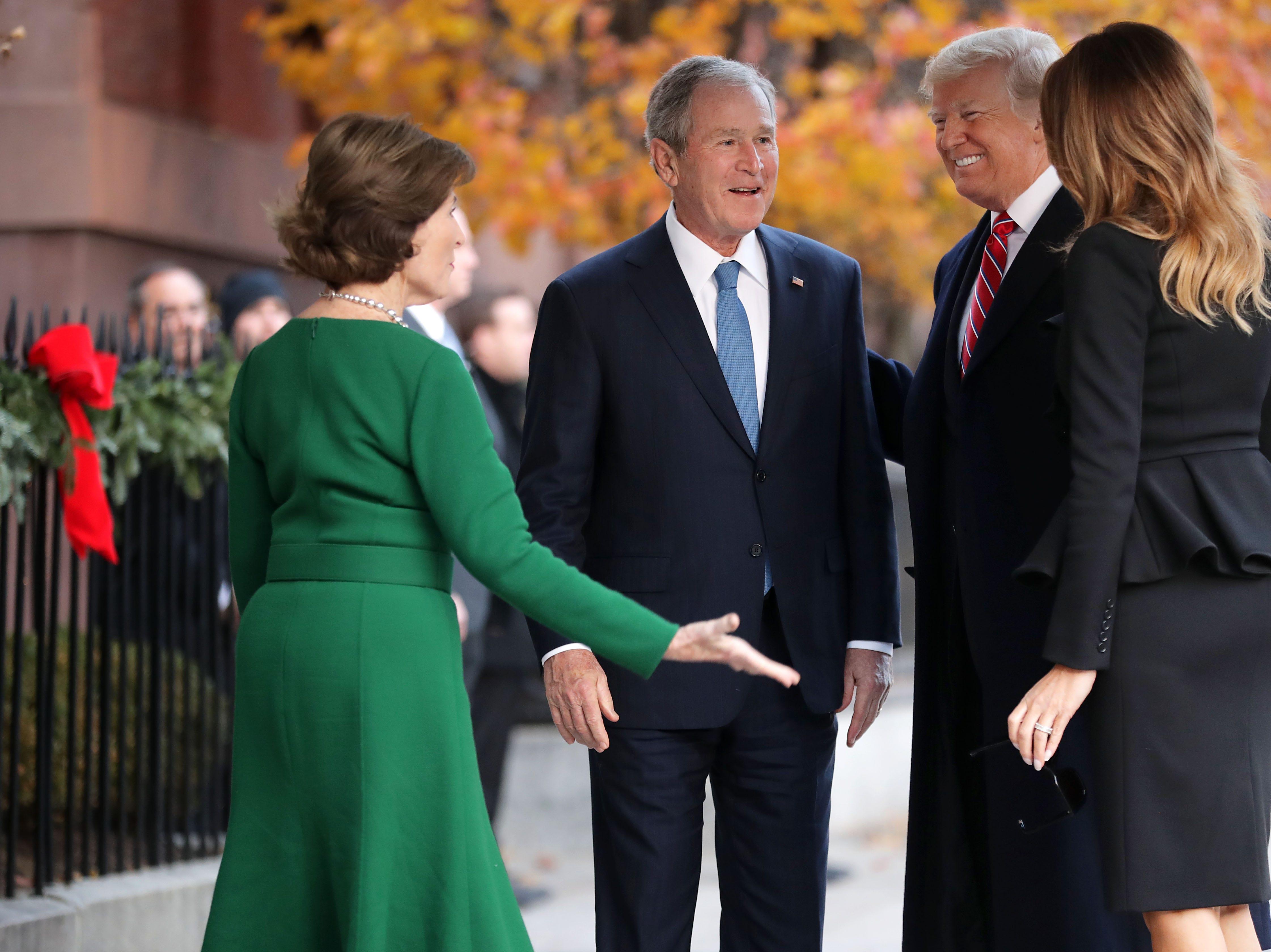 La ex primera dama Laura Bush y el ex presidente George W. Bush saludan al presidente Donald Trump y a la primera dama Melania Trump en las afueras de Blair House el 4 de diciembre de 2018 en Washington, DC.