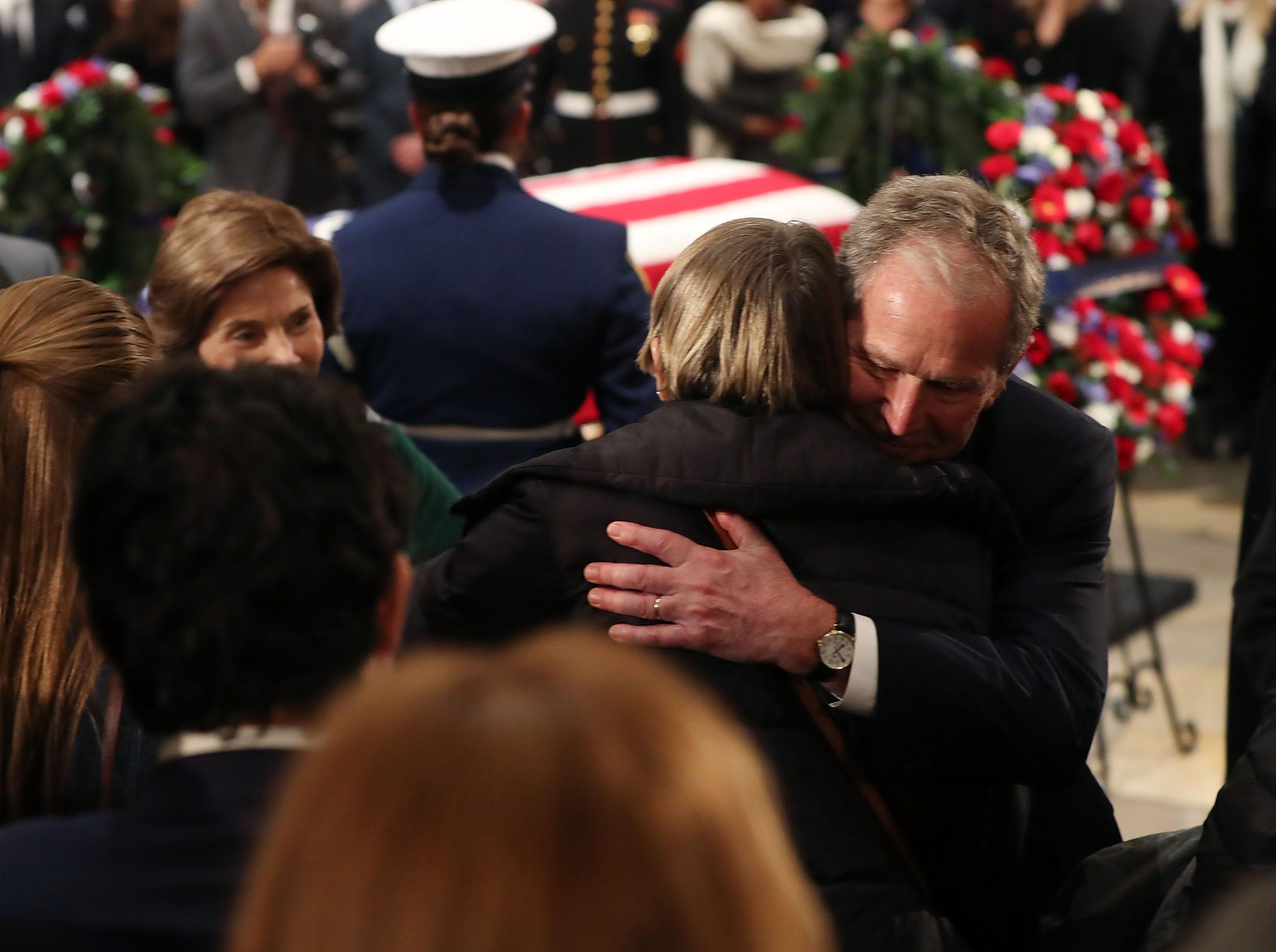 El ex presidente de los Estados Unidos, George W. Bush, y su esposa, Laura Bush, saludan a los asistentes frente al ataúd del fallecido ex presidente George H.W. Bush en la Rotunda del Capitolio de los Estados Unidos, el 4 de diciembre de 2018 en Washington, DC.