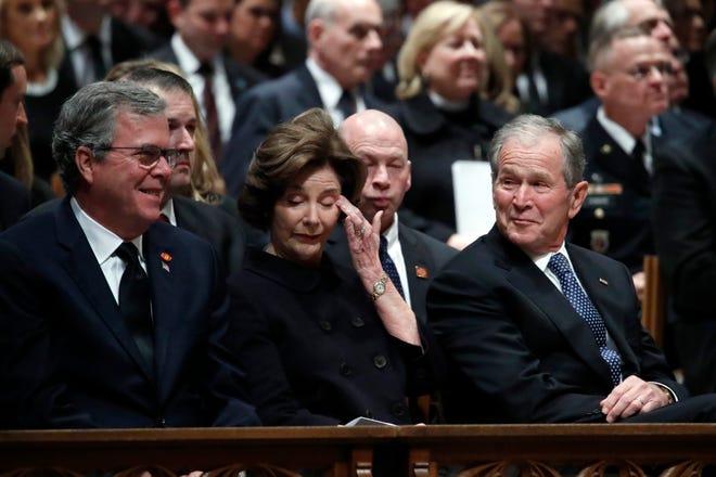 Former Gov. Jeb Bush, former First Lady Laura Bush and former President George W. Bush share a moment at the funeral for former President George H.W. Bush.