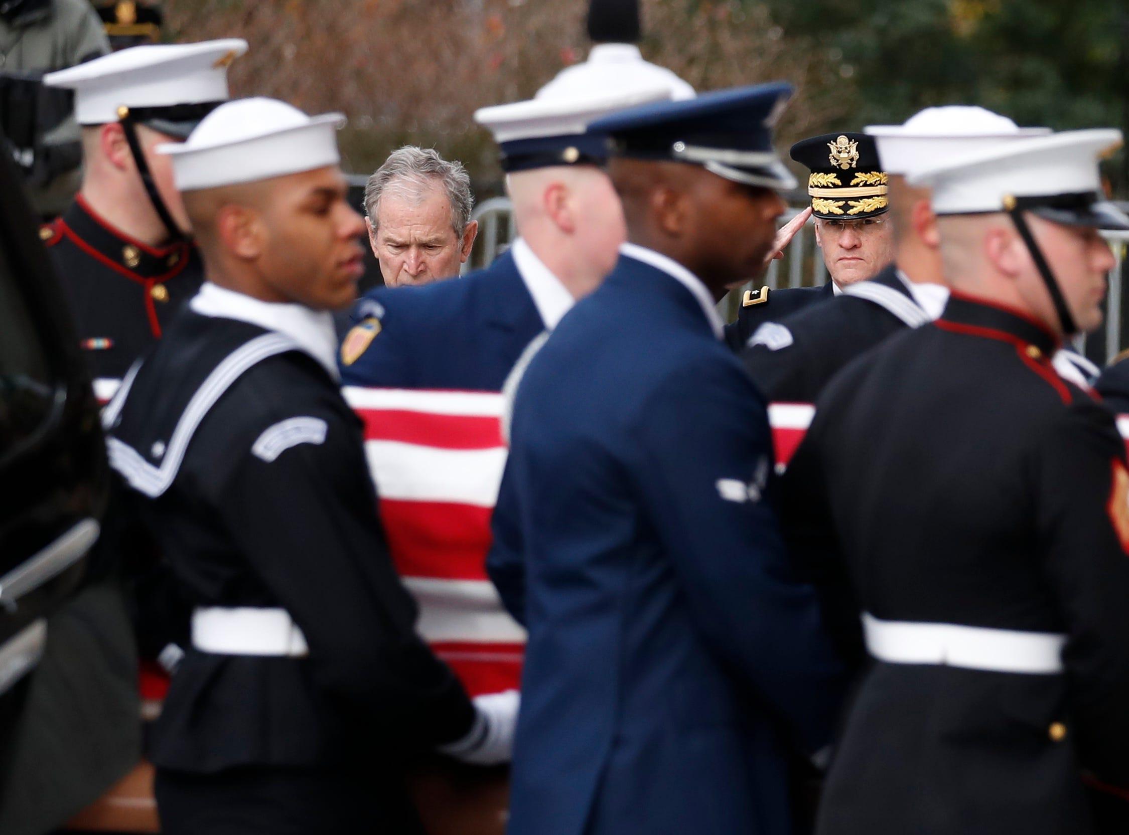 El ex presidente George W. Bush ve como el ataúd cubierto con la bandera del primer presidente George H.W. Bush es llevado por una guardia de honor militar de servicios conjuntos a un funeral estatal en la Catedral Nacional el 5 de diciembre de 2018 en Washington, DC.