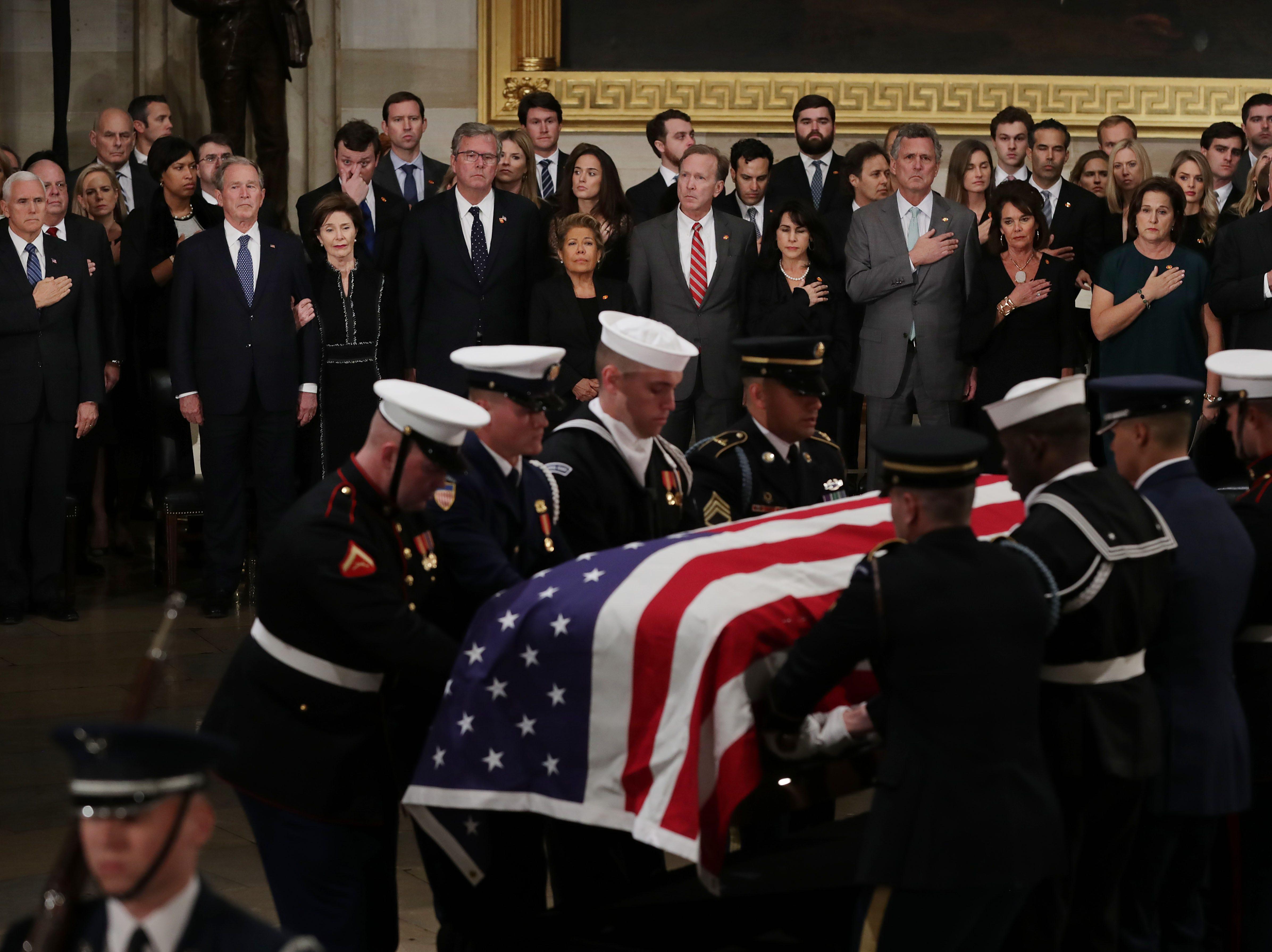 La familia del ex presidente de los Estados Unidos, George H.W. Bush se para mientras su ataúd cubierto con la bandera se lleva a la Rotonda del Capitolio de los EE. UU. Durante una ceremonia de llegada el 3 de diciembre de 2018 en Washington, DC.