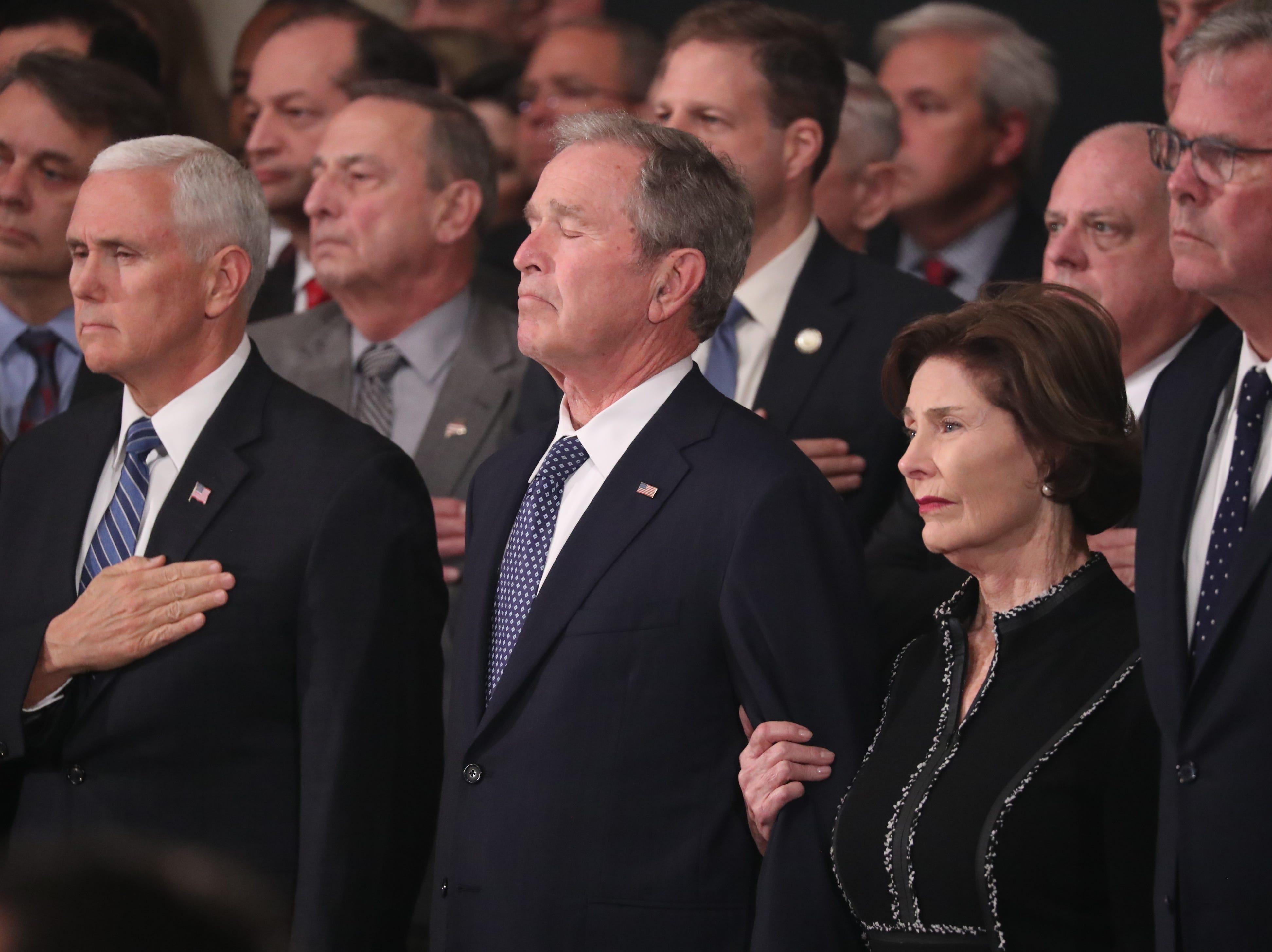 El vicepresidente Mike Pence, el ex presidente George W. Bush, la ex primera dama Laura Bush y el ex gobernador de Florida Jeb Bush observan como el ataúd del ex presidente George H.W. Bush llega a residir en el estado en la Rotunda del Capitolio de los EE. UU. el 3 de diciembre de 2018 en Washington, DC.