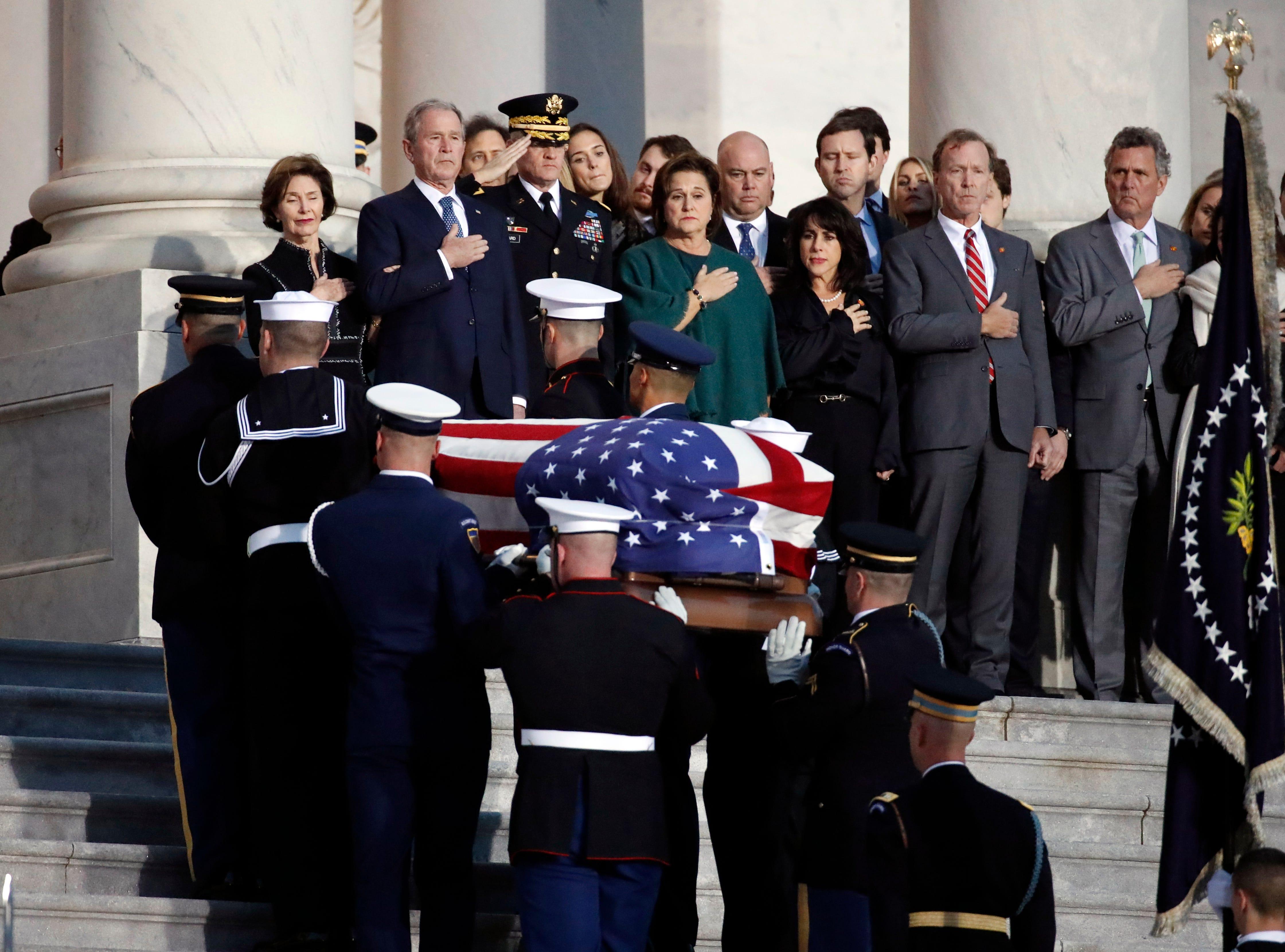 La ex primera dama Laura Bush (L), el ex presidente de los EE. UU. George W. Bush (L) y otros miembros de la familia observan cómo un equipo de la guardia de honor militar lleva el cofre del ex presidente de los EE. UU., George H.W. Bush entró en el Capitolio de los Estados Unidos el 3 de diciembre de 2018 en Washington, DC.