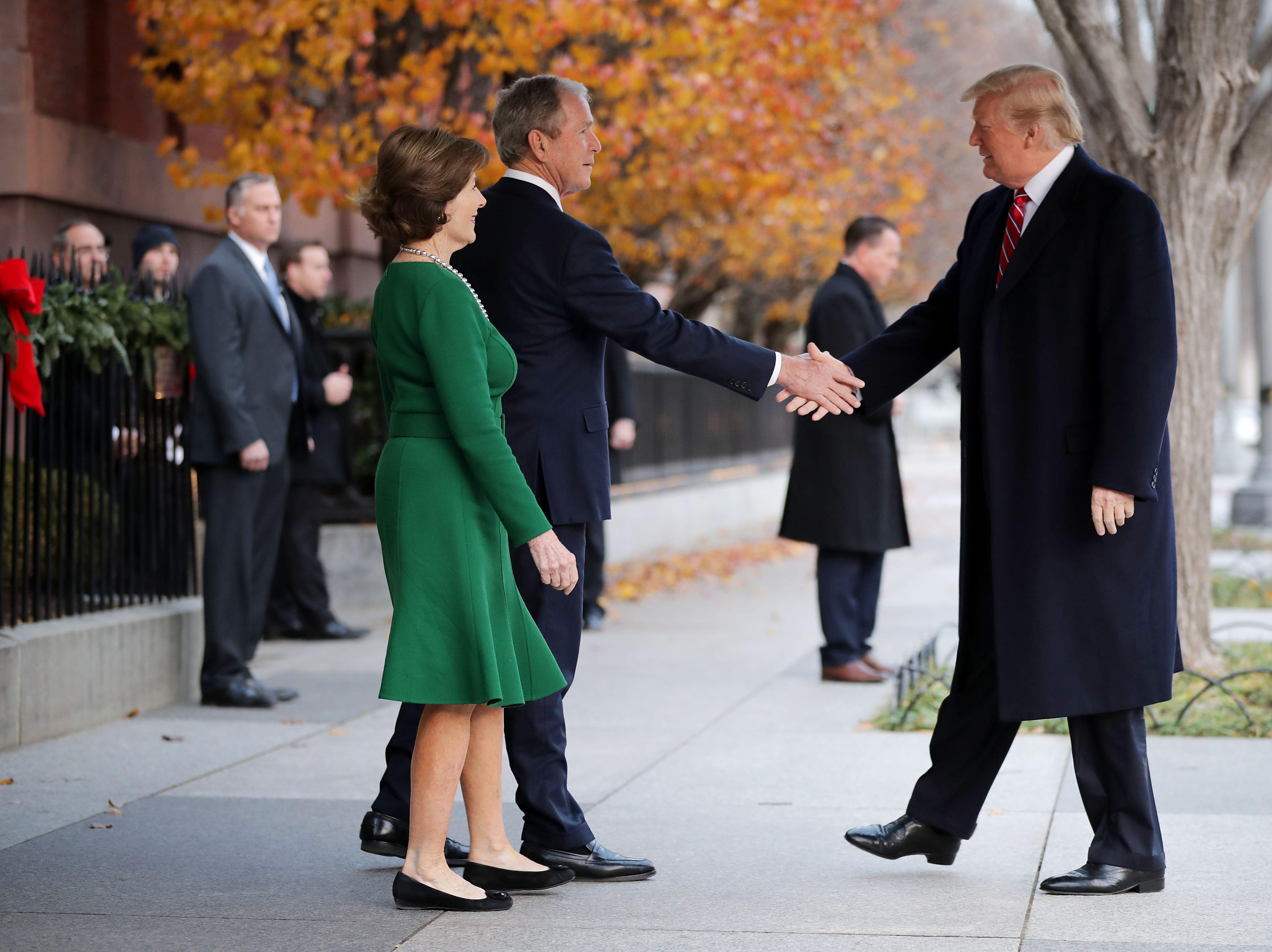 La ex primera dama Laura Bush y el ex presidente George W. Bush saludan al presidente Donald Trump en las afueras de Blair House el 4 de diciembre de 2018 en Washington, DC.