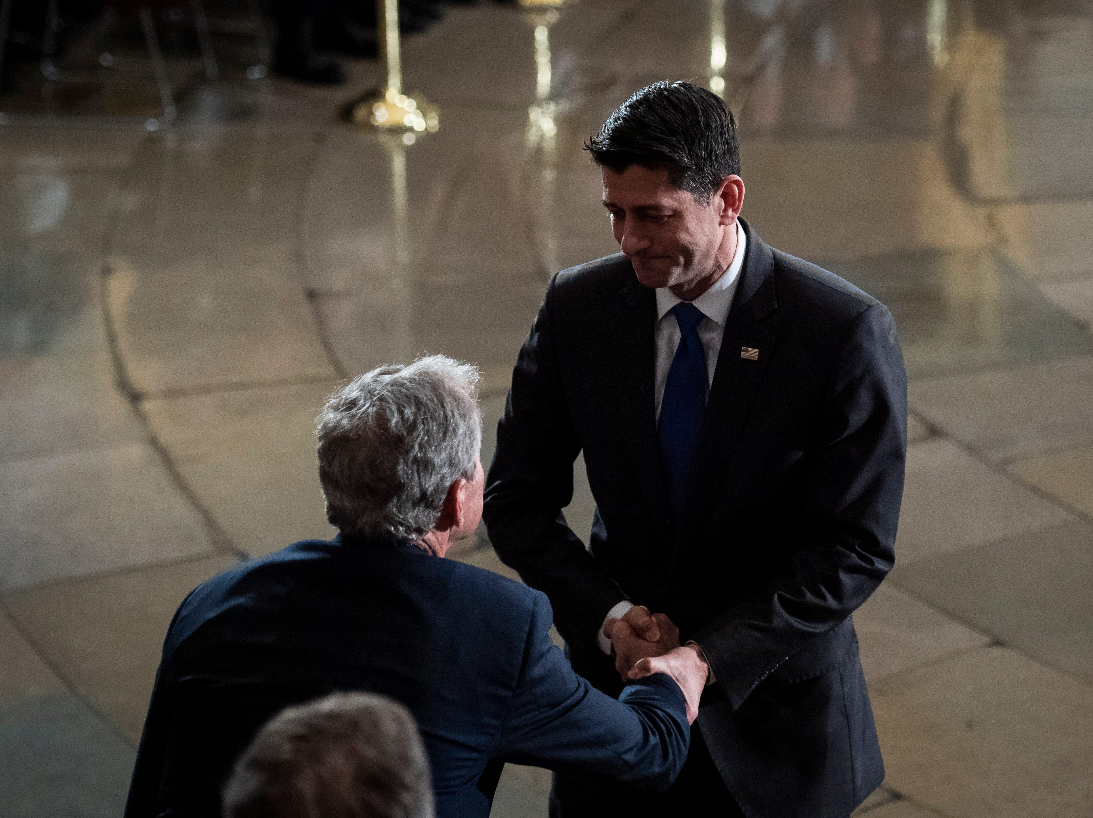 El representante de la Cámara de Representantes, Paul Ryan (der), saluda al ex presidente de los Estados Unidos, George W. Bush, durante una ceremonia para el ex presidente de los Estados Unidos, George H.W. Bush en la Rotonda del Capitolio de los Estados Unidos el 3 de diciembre de 2018 en Washington, DC.