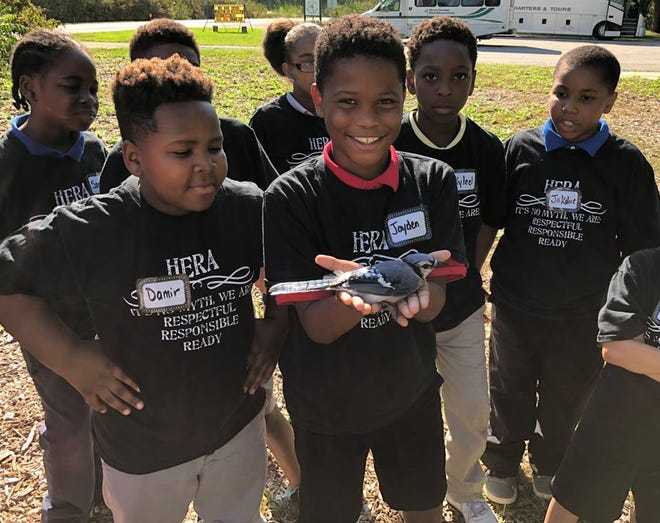 A class from the Chase STEM Academy in Toledo hold and examine a blue jay during an education program organized by the Black Swamp Bird Observatory.