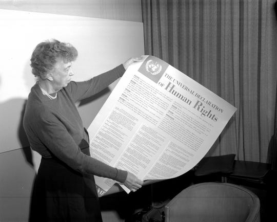 Eleanor Roosevelt holding a Declaration of Human Rights poster.