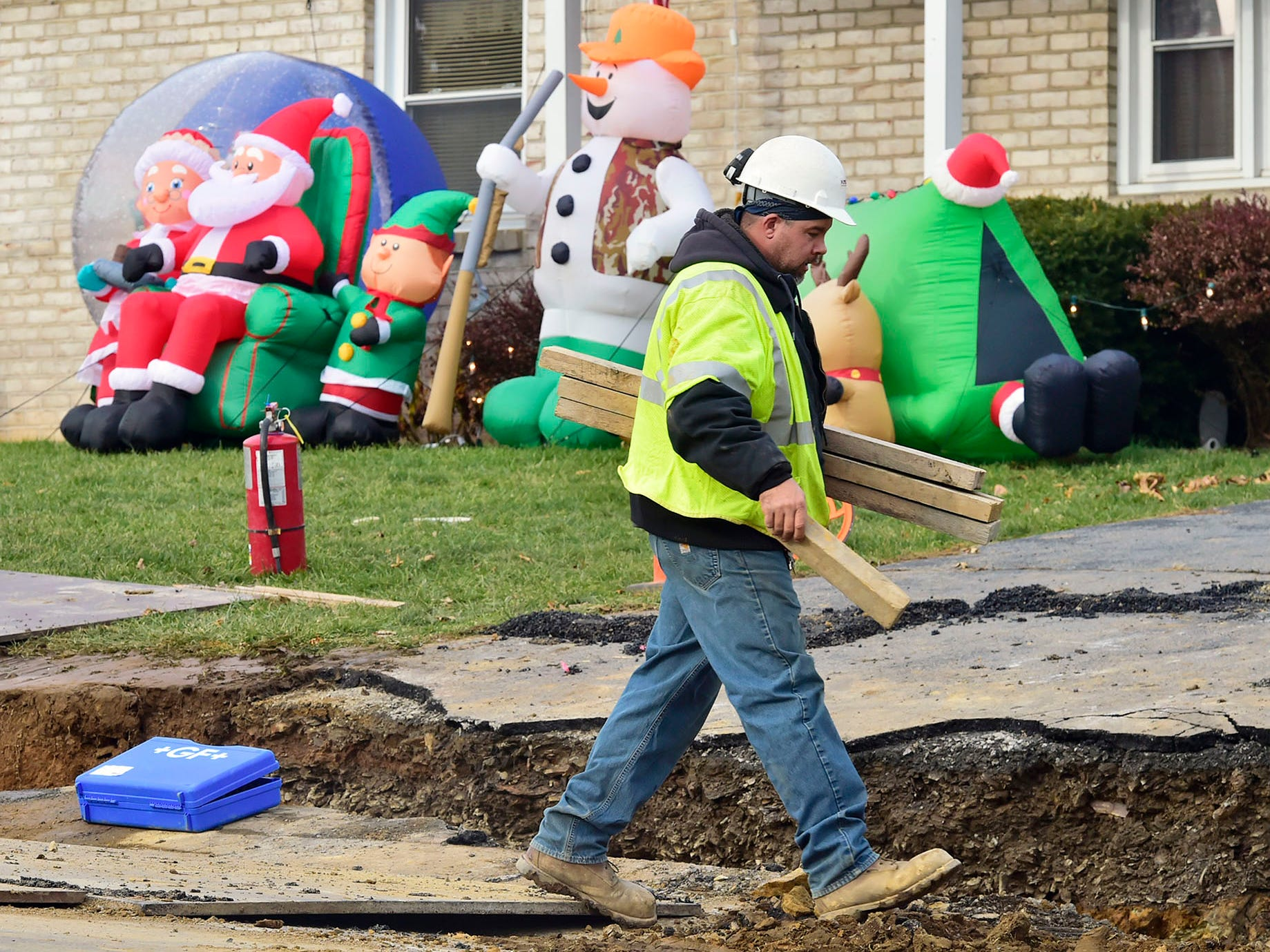 Christmas decorations are seen in the background as Kinsley Construction Co. employees install gas lines along the 2000 block of Main Street in Fayetteville on Wednesday, December 5, 2018.