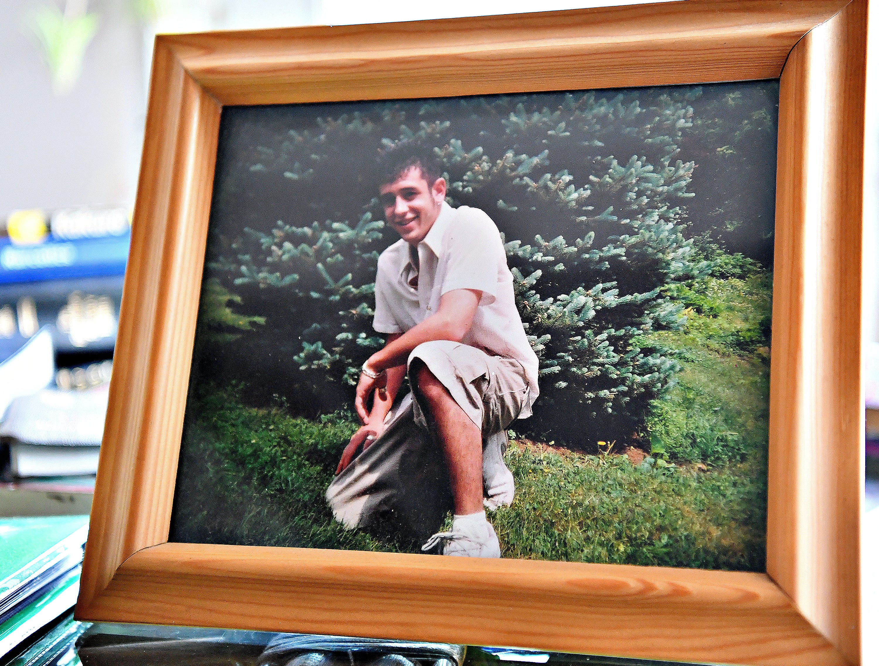 Alexander Lauer's senior picture amongst photo albums, journals and a plethora of notes and other research materials span the kitchen table at the Lauer home in York Township, Tuesday, Dec. 4, 2018. The materials belonged to Alexander Lauer, 33, who lost his decade-long battle with heroin unexpectedly on Nov. 20., just one week after being released from York Hospital for drug treatment. Dawn J. Sagert photo