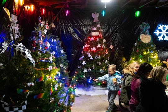 Guests take a break in a room filled with Christmas trees at Christmas Magic 2018 at Rocky Ridge County Park in Springettsbury Township.
