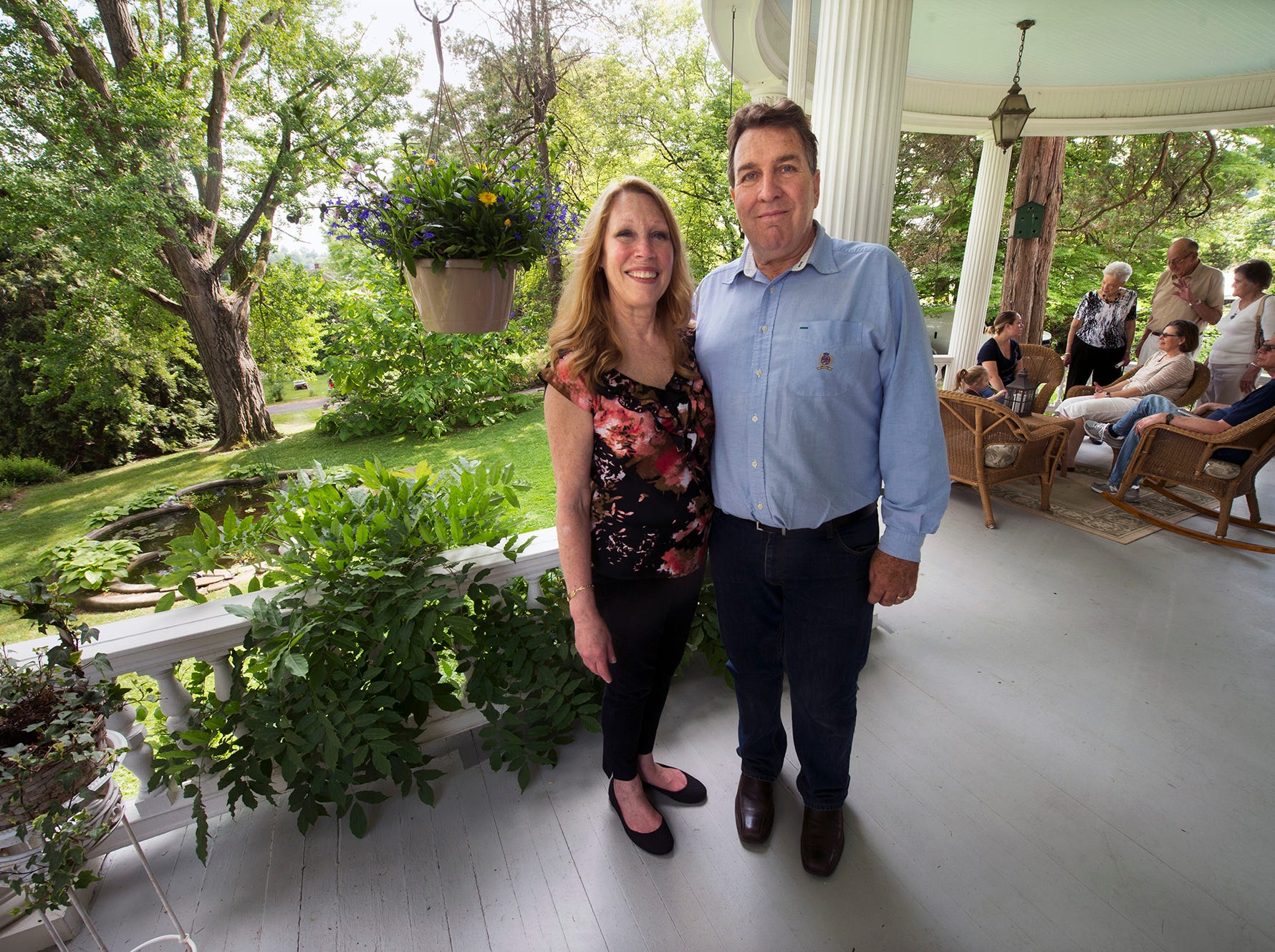Innkeepers Lori, left, and Bill Fitzell stand on the large wrap-around porch during an open house at the Emig Mansion Bed & Breakfast on Sunday May 17, 2015.