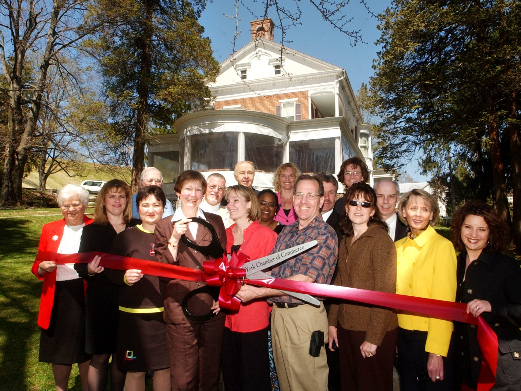 Shary Smith holds giant scissors with the help of her daughter, Heather Welsh, center front, and her husband, Wade Lady, to Welsh's right, as they are surrounded by friends, business associates and others during ribbon-cutting ceremony at the Emig Mansion staged by York County Chamber of Commerce. Smith bought the mansion in 2004 with her husband.