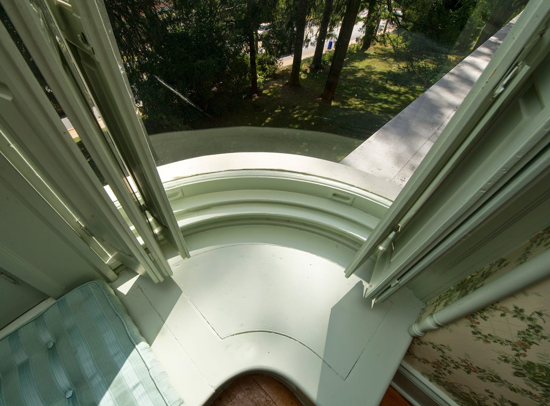 Curved glass wraps around a bay window on the second floor of the Emig Mansion.