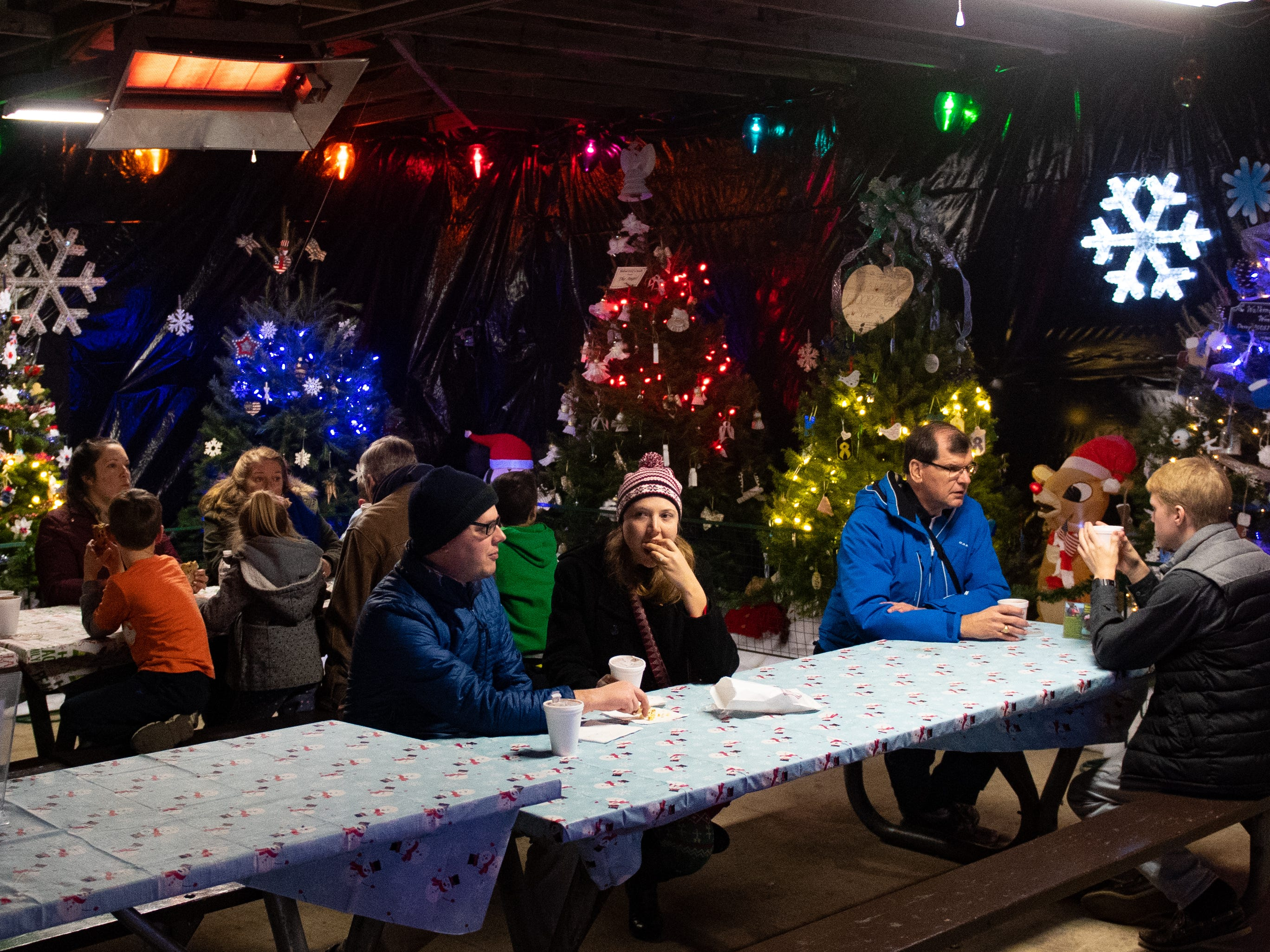 Guests take a break in room filled with Christmas tries at Christmas Magic 2018 at Rocky Ridge County Park in Springettsbury Township, Thursday, November 29, 2018.