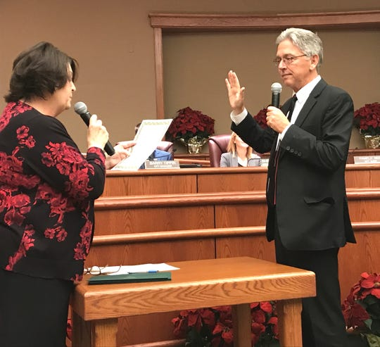 City Clerk Pam Mize gives the oath of office to new Redding City Council member Michael Dacquisto, right, on Tuesday night.